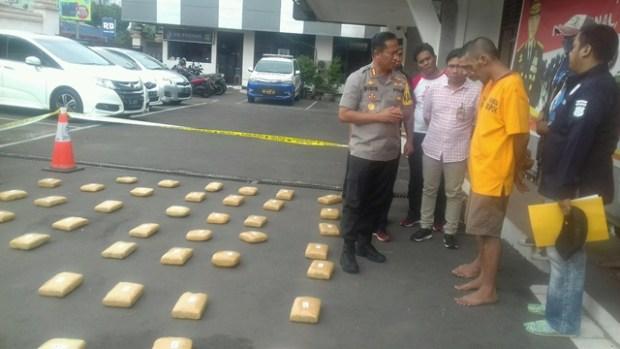 Kapolres Depok, Kombes Didik Sugiarto dengan latar belakang bungkusan ganja kering yang berhasil diamankan.