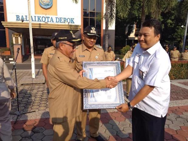 Walikota Depok menerima sertifikat ISO untuk Disdukcapil dan DPMPTSP.