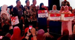 Presiden Jokowi didampingi Mensos dan Wakil Walikota Depok menyerahkan dana program keluarga harapan di Depok.