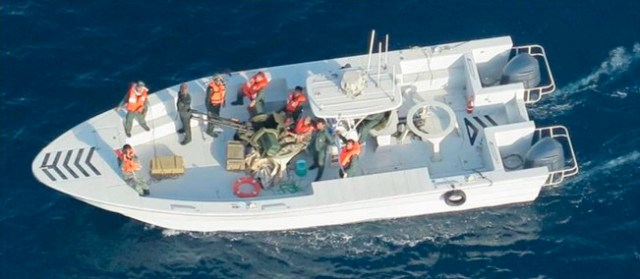 This image released by the U.S. Department of Defense on June 17, 2019, and taken from a U.S. Navy helicopter, shows what the Navy says is the Islamic Revolutionary Guard Corps Navy after removing an unexploded limpet mine from a tanker in the Strait of Hormuz.