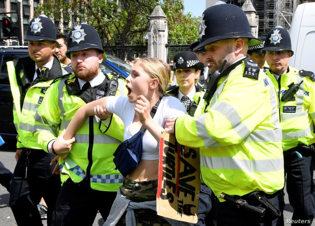 FILE - Police remove a climate change demonstrator during a march supported by Extinction Rebellion in London, Britain. May 24, 2019.