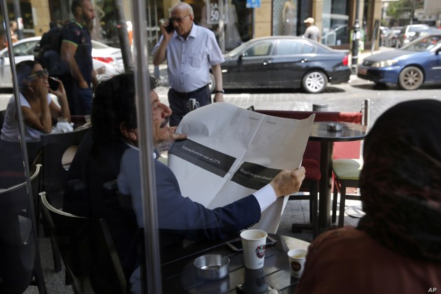 A man looks through a copy of the Lebanese local English-language newspaper, The Daily Star, in Beirut, Lebanon, Aug. 8, 2019.
