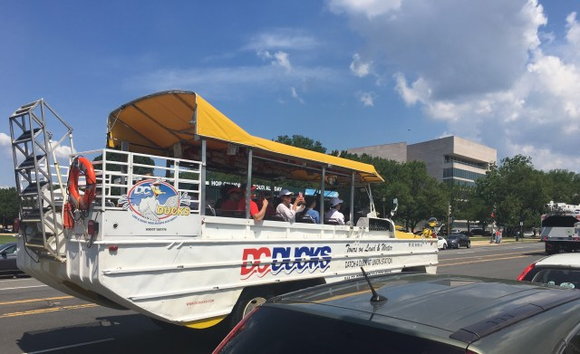 Tourists take photos of the U.S. Capitol (not seen) from a tour boat-like bus on a hot day in  in Washington, DC. (Photo by Diaa Bekheet)