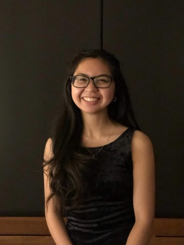 photo of a girl with long dark brown hair. She is wearing a black dress with glasses smiling.