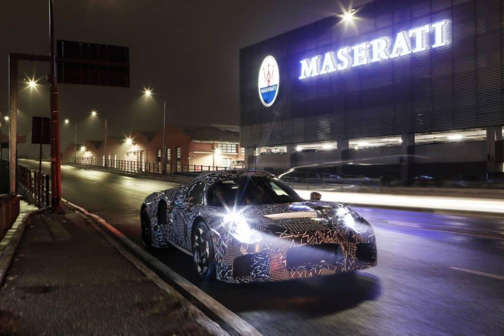 """Das erste Erprobungsfahrzeug in der Entwicklung eines neuen Maserati Motors verließ heute das Werksgelände an der Viale Ciro Menotti in Modena. Der Erlkönig weist nicht nur die typische Camouflage-Beklebung auf, sondern verweist mit einem """"Save the Date"""" auf sein Debüt, das für Mai 2020 geplant ist. Die Versuchsfahrzeuge sind mit einem neuartigen Motor ausgestattet. Er befindet sich in der hinteren Fahrzeugmitte. Der Antriebsstrang - gekennzeichnet durch ein innovatives Verbrennungssystem - wird vollständig von Maserati entwickelt und gebaut. Er wird zum Urvater einer neuen Motorenfamilie werden, die ausschließlich in den Fahrzeugen der Marke zum Einsatz kommt. Die Daten der von den Erprobungsfahrzeugen zurückgelegten Strecken werden in die Fahrsimulatoren des Maserati Innovation Lab integriert. Diese Methode wird genutzt, um Prototypen mit endgültiger Karosserieform und Technologie zu entwickeln."""
