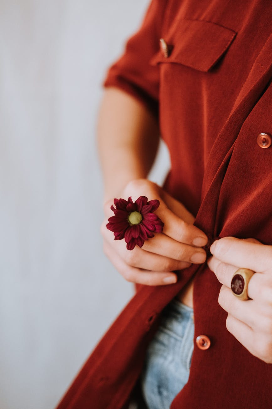 woman with gentle flower on hand buttoning blouse