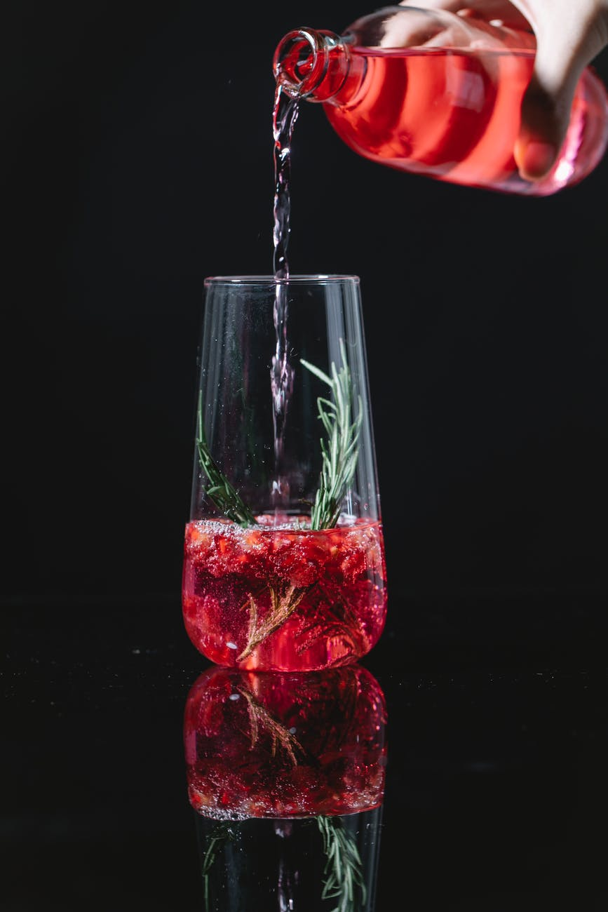 crop barman pouring drink into glass