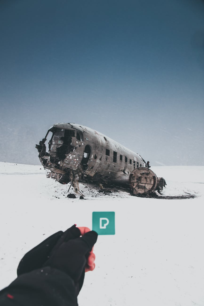 faceless person showing sticker against crashed airplane in winter