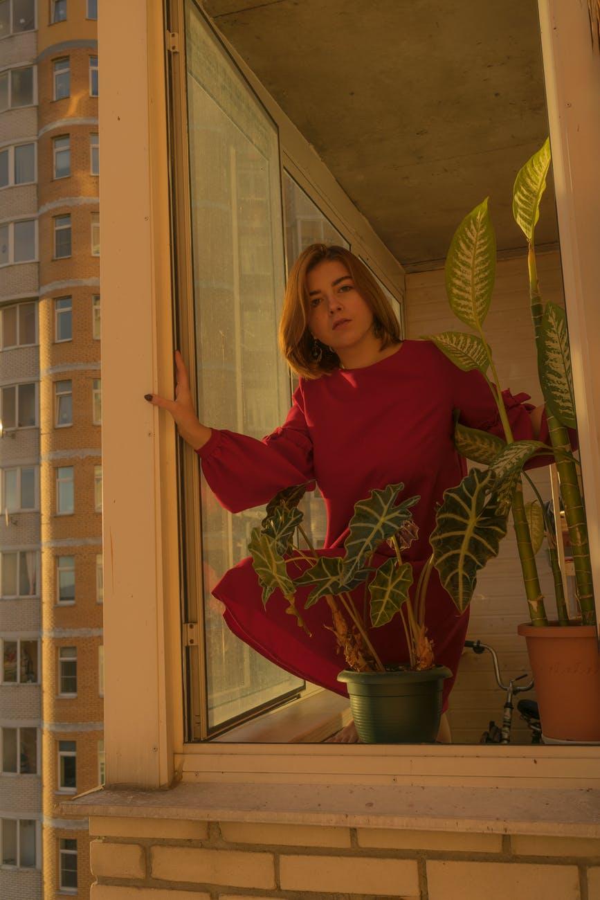 woman standing near window in balcony