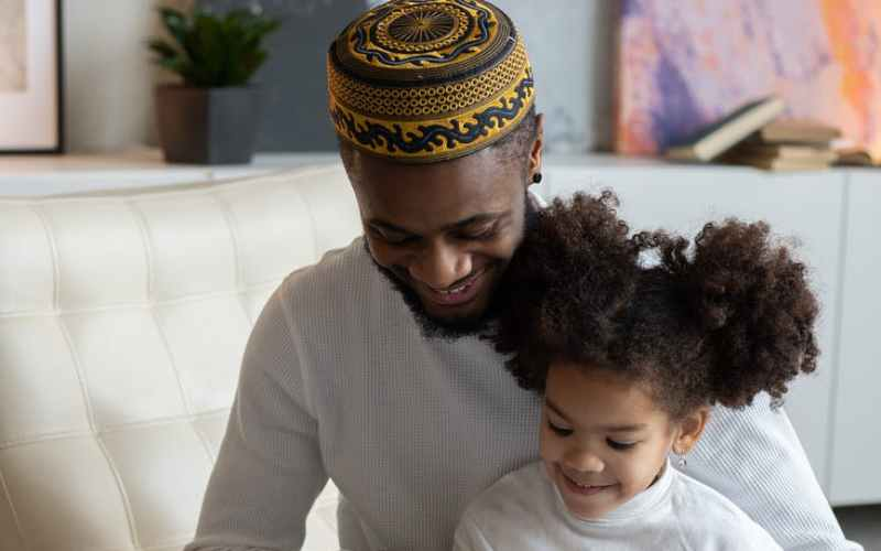 delighted black father reading book to positive daughter