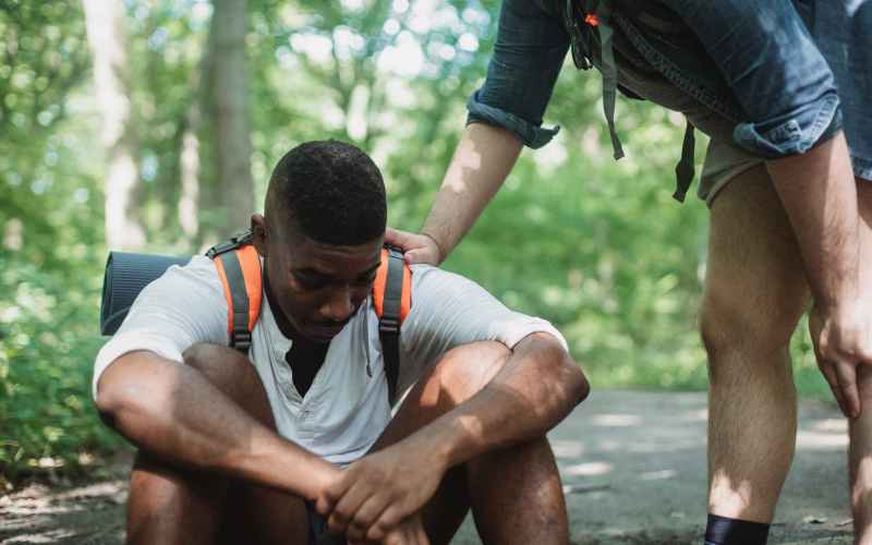 unhappy black hiker sitting on ground in forest