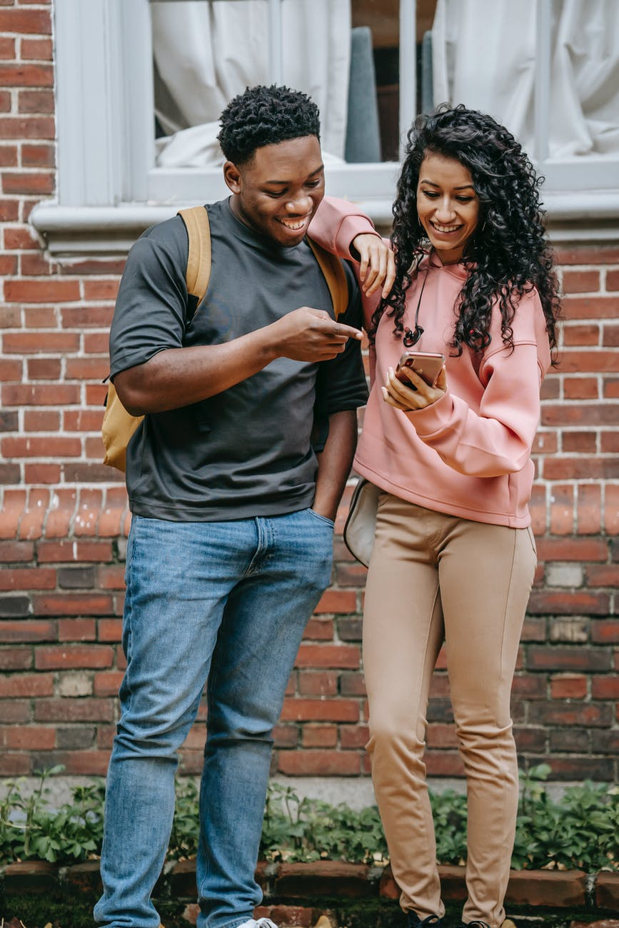 happy diverse students sharing smartphone together and smiling