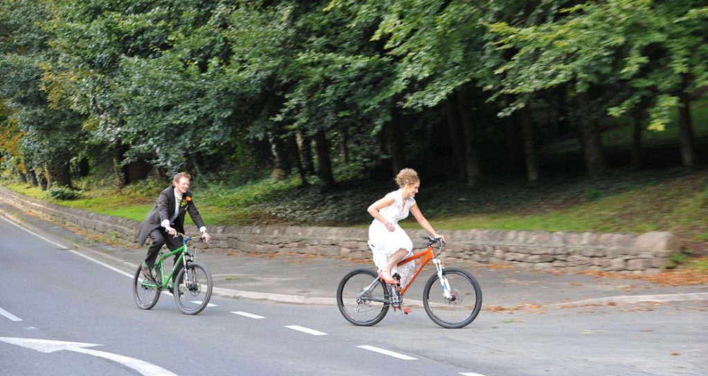A newly married Bride and Groom ride on the street on mountain bikes