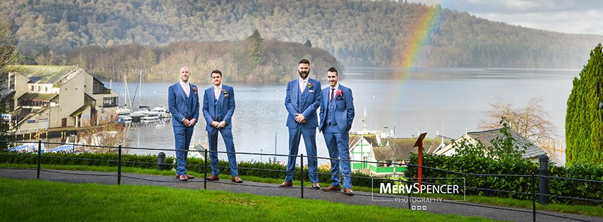 A Groom stands with his Best man and two Groomsmen against a rainbow with a background of a harbour