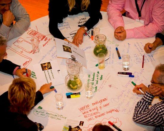 World Cafe methode Thematafels Tegenlicht Den Haag mensen aan tafel die het doen