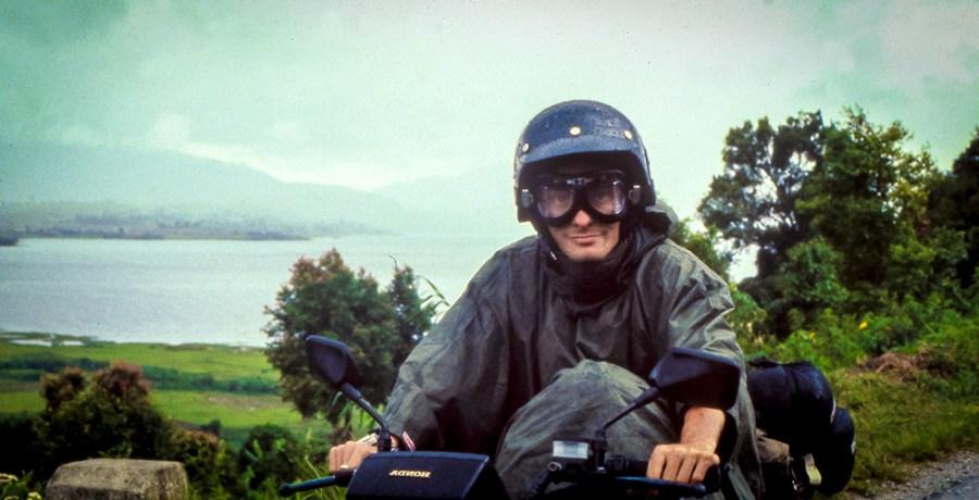 Motorradfahrer mit Regenponcho, Jethelm und Motorrasbrille. Im Hintergrund ein See.