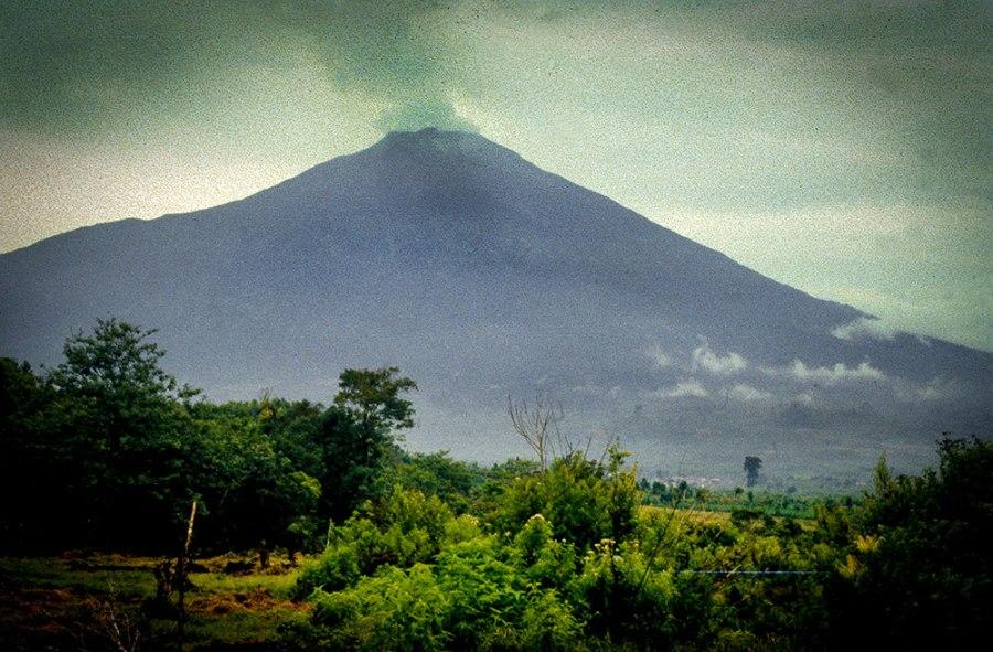Rauchender Vulkan und grünne Wälder.