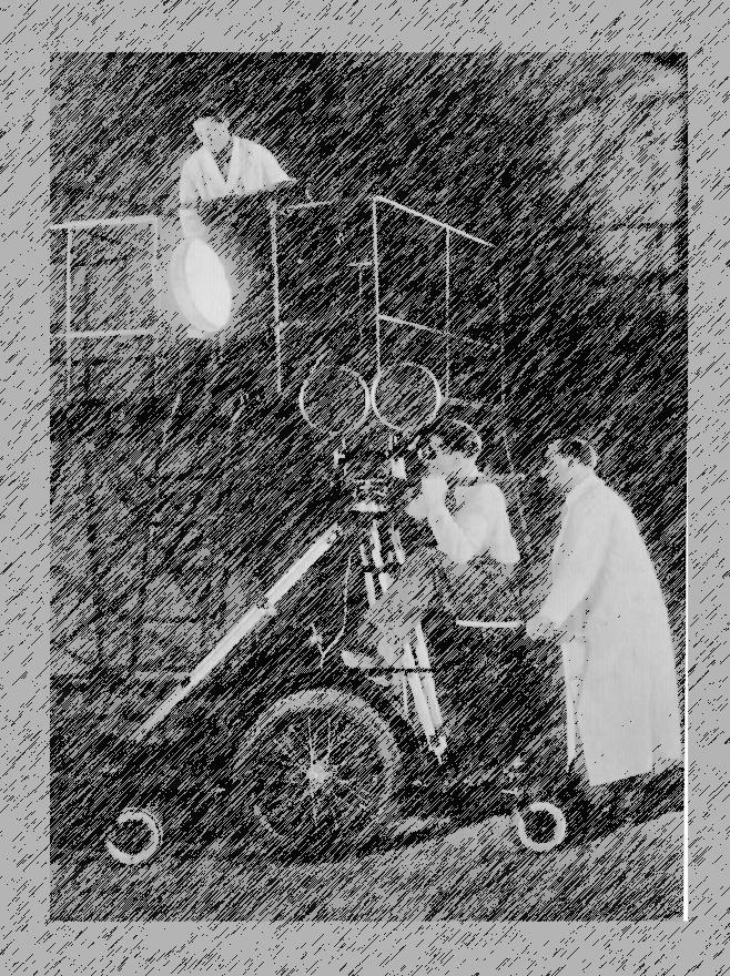 Beleuchter, Kameramann auf einem altertümlichen Dolly mit Kamera und Stativ. Ein Helfer im weissen Kittel schiebt die Konstruktion.