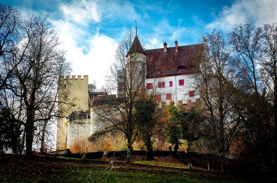 Die Lenzburg an einem sonnigen Febuartag: wolken am blauen Himmel und kahle Bäume.