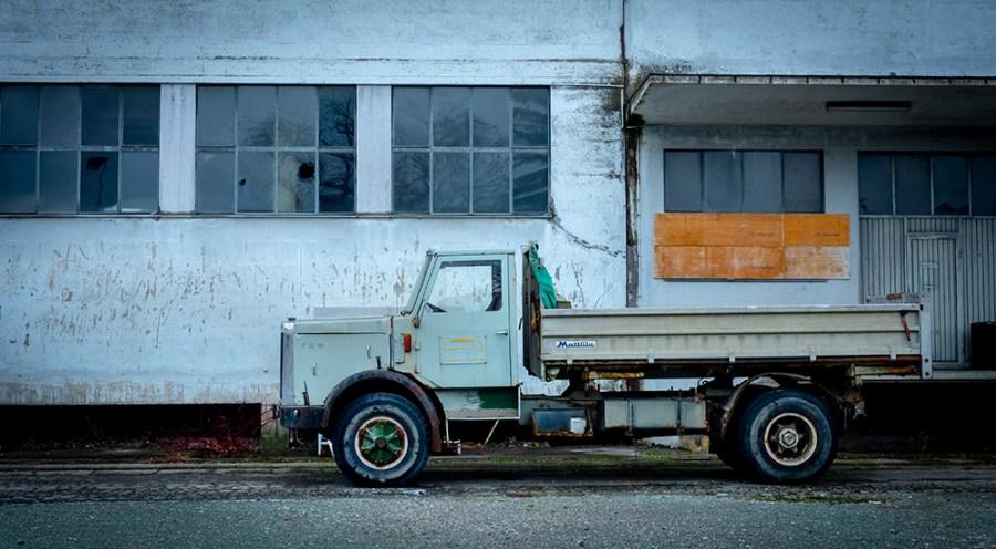 Ein alter Lastwagen vor einem verlassenen Industriegebäude.