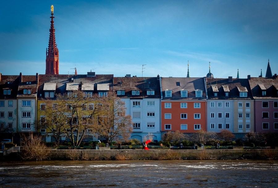 Mainufer, Kirchturm. Frau im roten Kleid mit roten Luftballons, blauer Himmel