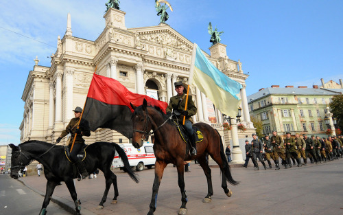 Wearing the uniform of the Ukrainian Insurgent Army, known by its Ukrainian acronym UPA, nationalists march with their red-black (L) and Ukrainian national yellow-and-blue (R) flags in the western Ukrainian city of Lviv, on October 10, 2010, to mark the anniversary of World War II rebels who fought the Soviets. The UPA -- which was founded in 1942 and at one point numbered around 40,000 fighters -- initially welcomed the German invasion of the Soviet Union as a liberation from Communist rule. It later turned against Berlin, but when the Soviet Red Army swept back into Ukraine the UPA fought against it too, continuing its attacks until well after the end of World War II. AFP PHOTO/ YURIY DYACHYSHYN (Photo credit should read YURIY DYACHYSHYN/AFP/Getty Images)