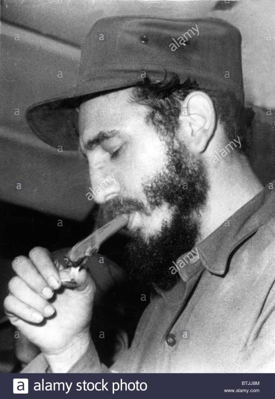 FIDEL CASTRO, lighting a cigar, 1967