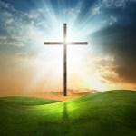 Christian cross above grass field at sunset.
