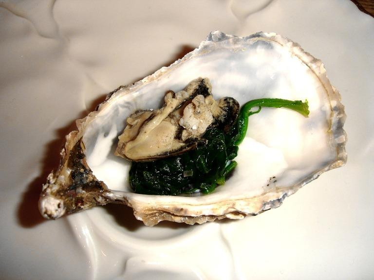 pochierte Auster auf Blattspinat
