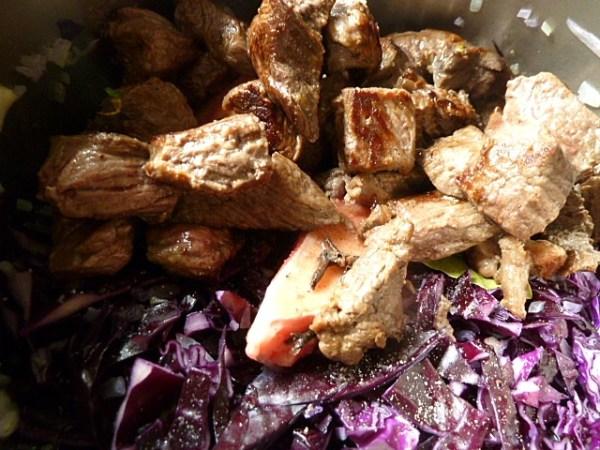 Das angebratene Fleisch zum Kraut geben und aufgießen
