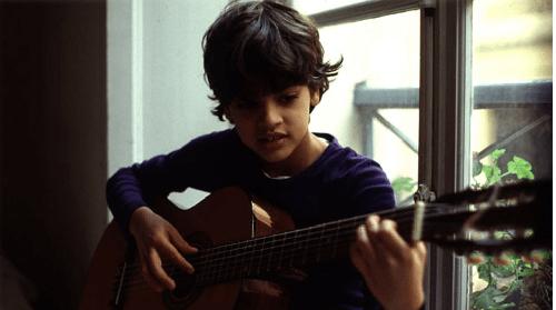 André Stern enfant en train de jouer de la guitare.