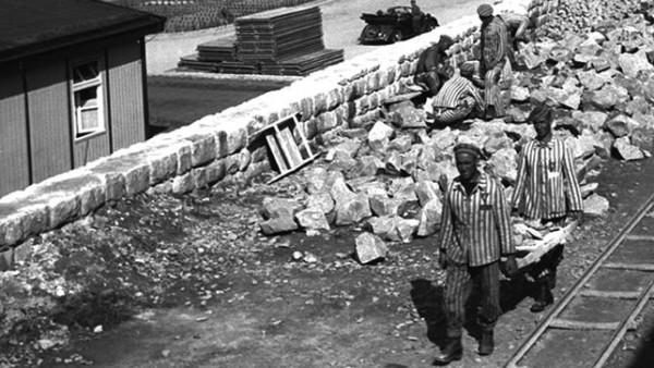 Prisioneiros de Mauthausen transportam pedras para a construção do campo
