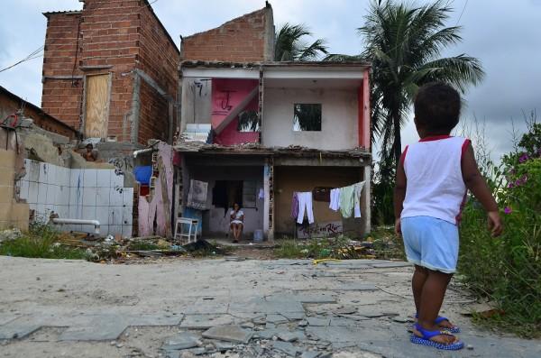 Família em meio a escombros de casas destruídas na Vila Autódromo no Rio de Janeiro em março