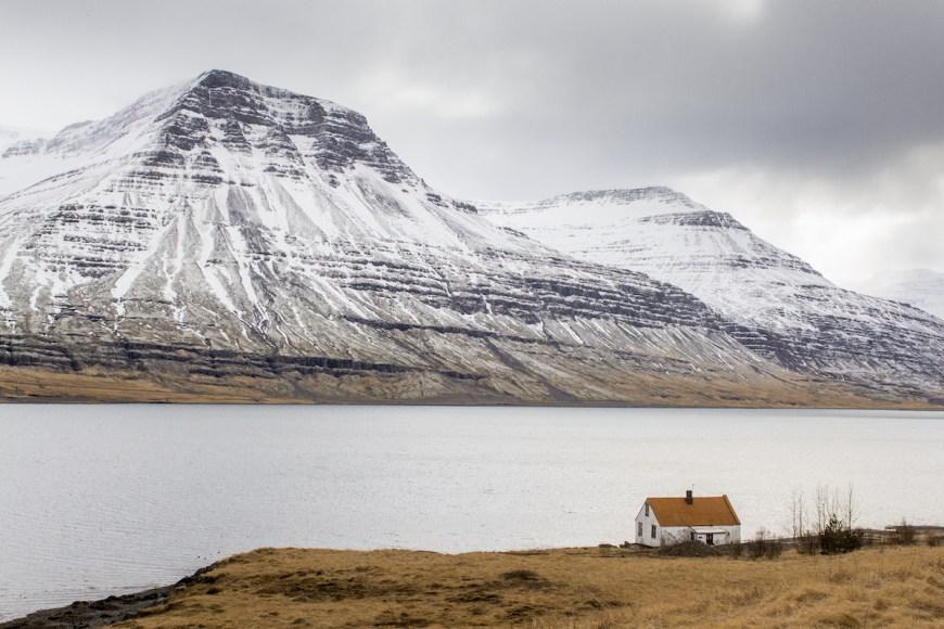 Islandia, montaña con un lago y una casa con el tejado rojo