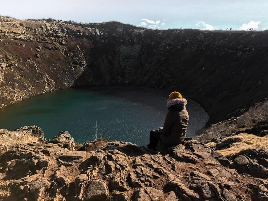 Anna sentada en el borde del Kerid Crater en el circulo dorado de Islandia