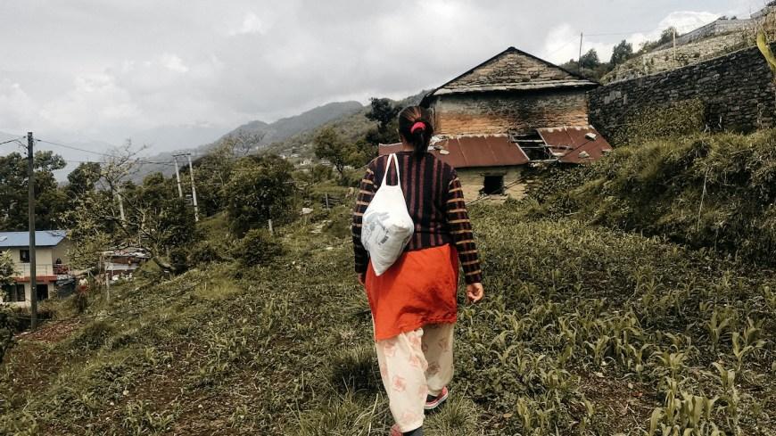 Mujer nepalí caminando entre campos en el Sarangkot, Nepal