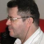Imagem de David com rosto sorridente, visto de perfil. O cabelo anteriormente raspado, já voltou a crescer. Ele usa óculos de grau e a parte externa do IC está ligada por um fio ao computador, para fazer a programação necessária.