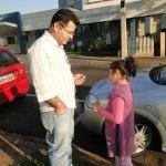 Imagem de David com a filha de 6 anos. Eles estão na calçada, em frente a dois carros. Do outro lado da rua, é possível ver algumas casas. David e a filha estão de frente uma para o outro e, nas mãos de David, está o controle remoto do aparelho dele.