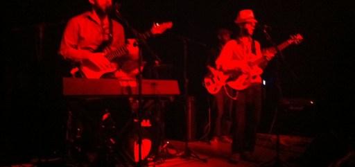 Imagem borrada dos músicos. Dá pra ver apenas a silhueta avermelhada deles no palco.