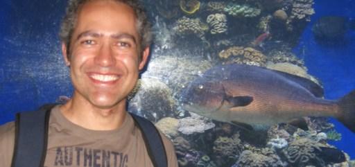 Imagem de Fernando Cabral olhando para a câmera e sorrindo. Fernando tem cabelos curtos e já grisalhos, rosto sorridente e de feições bem marcadas, ele veste uma camiseta e é possível ver as alças da mochila que carrega nos ombros. Ao fundo, uma parede de aquário gigante, com peixes nadando e decoração marinha: pedras, plantas e algas.
