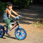 Kadu na bicicleta azul, em algum parque.