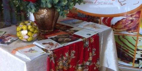 """Imagem da mesa da entrada do evento. Quadrada, com uma toalha branca e outra vermelha com flores estampadas sobreposta. Sobre a mesa, vários folhetos de aparelhos de implante coclear, um grande arranjo de flores e um vaso redondo de vidro, com bolinhas amarelas no inteior. Ao fundo, pode-se ver uma placa com o nome do restaurante """"Tempero"""""""