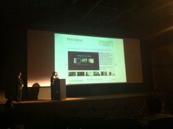 Imagem de um palco, com uma tela no fundo onde aparece a apresentação do projeto, com vídeos e explicação. Duas moças estão no palco, atrás de um pequeno balcão, explicando sobre o projeto.