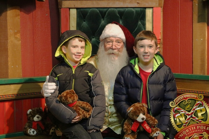 Santa Claus with two boys at the North Pole Experience