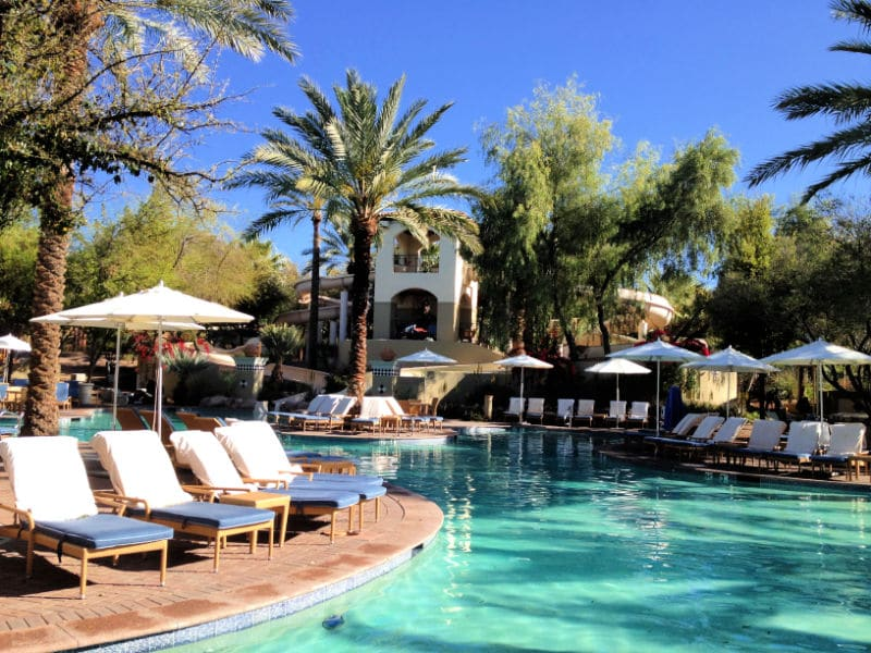Pool with umbrellas, chairs, palm trees and blue sky
