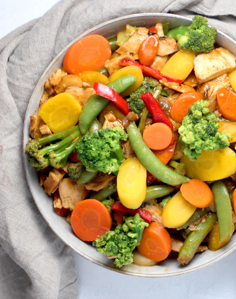 bowl of stir fry featuring veggies, rice and chicken