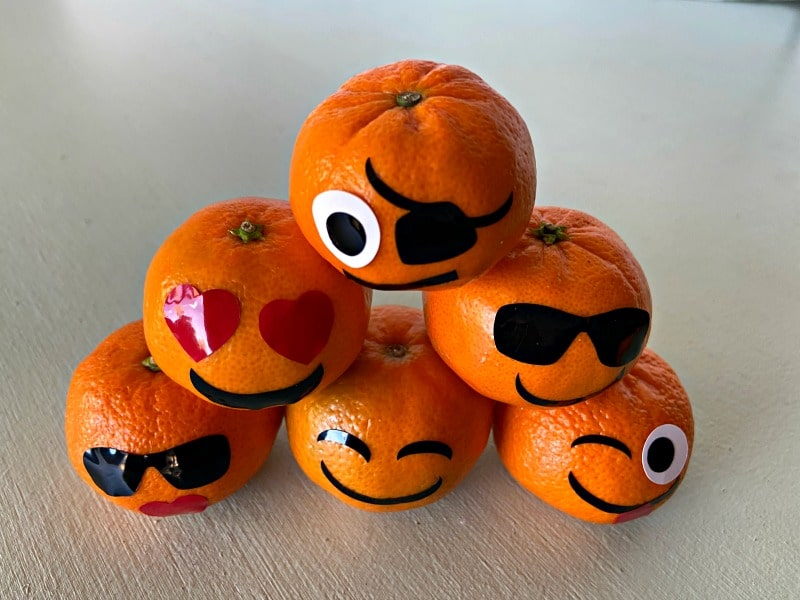 oranges decorated with emoji faces