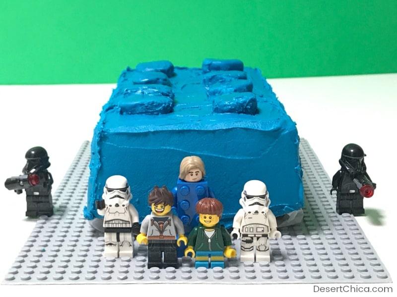 birthday cake shaped like a LEGO brick with lego minifigures decorating it
