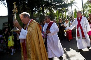 Fr. Christopher carries Blessed Sacrament; Fr. Brad sprinkles holy water.