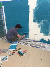 a volunteer helps paint the wall
